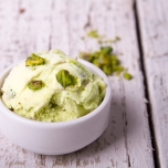 Scoop of pistachio ice cream in bowl on white wood