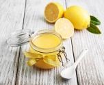 Lemon curd in glass jar with fresh lemons